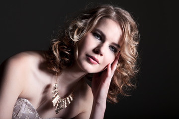 Hübsche junge Frau elegant gestylt blickt in die Kamera