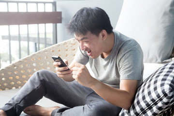 Asian man looking at his phone with an surprised expression