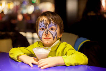 Little boy with painted face as butteffly, eating ice cream