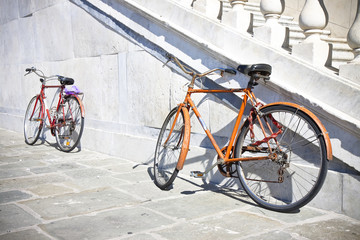 Two old rusty bicycles against a marble wall (Tuscany - Italy)