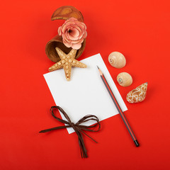 Card with flowers, shells and pencils on red background