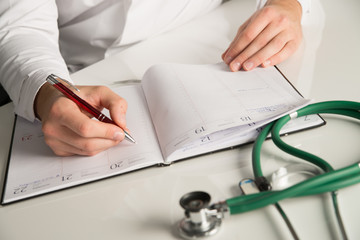 doctor writing at note book