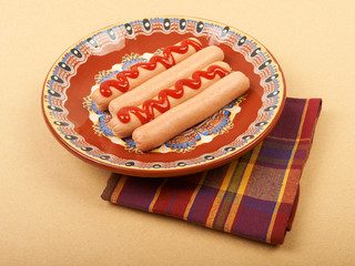 Boiled sausage with mustard on a plate