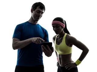 Wall Mural - woman exercising fitness  man coach using digital tablet  silhou