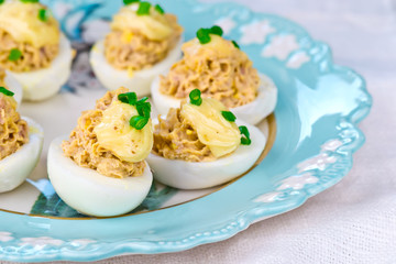 delicious stuffed eggs on blue plate.