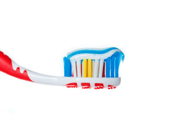 Red toothbrush with blue two color toothpaste on light surface