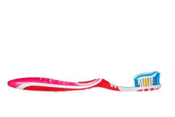 toothbrush with blue two color toothpaste on light