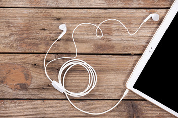 Tablet computer with earphones against wooden background