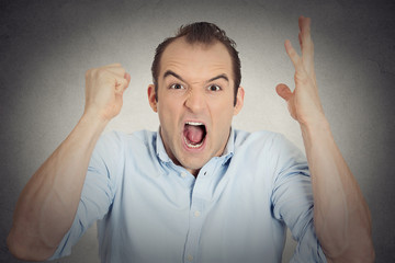 headshot angry upset young man fist in air open mouth yelling