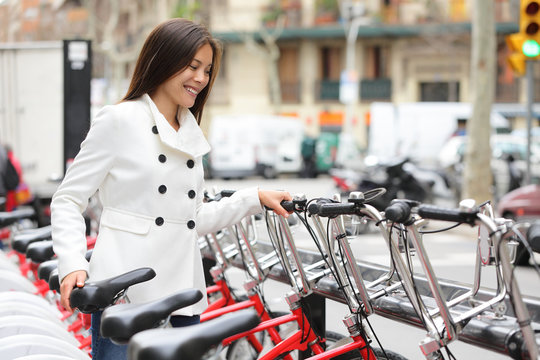 City bike - woman using public city bicycles