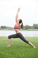 Woman practicing Warrior yoga pose outdoors on lawn,left side
