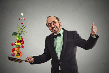 Businessman cooking vegetables with a pan grey background