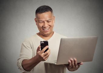 happy surprised man reading news on smart phone holding laptop