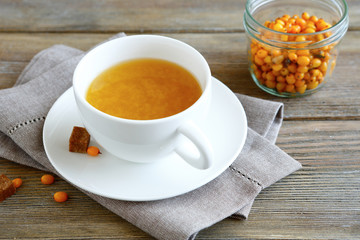 Sea-buckthorn tea in a cup on wooden boards