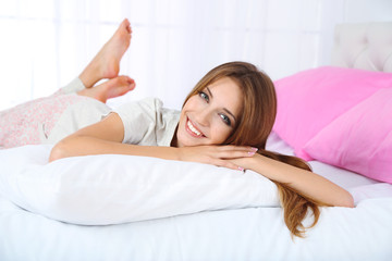 Young beautiful woman lying in bed