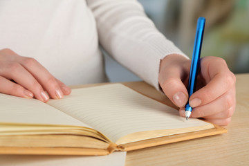 Female hand with pen and notebooks at wooden desktop