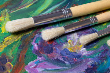 close up of paint brushes on canvas background
