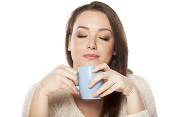 positive young woman enjoying the scent of a cup of tea