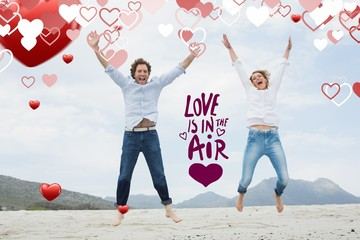 Composite image of cheerful young couple jumping at beach
