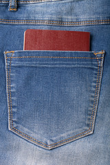 The pocket of jeans with document. Cloth background