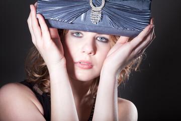 Junge hübsche Frau mit Tasche blickt sinnlich