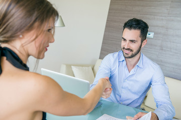 Man and Woman giving Handshake at Office