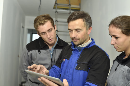 Electrician explaining trainees building electric plan