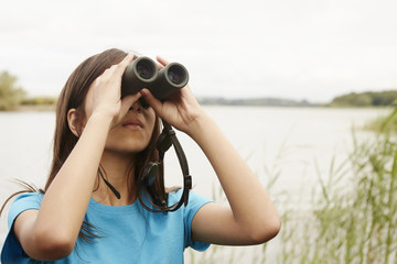 A young girl, a birdwatcher with binoculars.