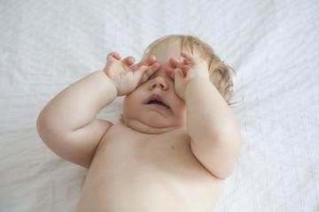 baby yawning on white bed
