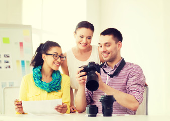 smiling team with photocamera working in office