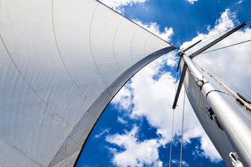 Mast and sail against the sky with clouds