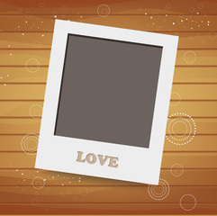 Blank instant photo on wood background