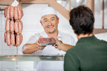 Butcher Giving Packed Sausages To Customer