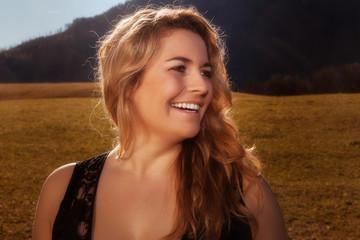 Portrait eines lachenden blonden Mädchen mit goldenem Haar.