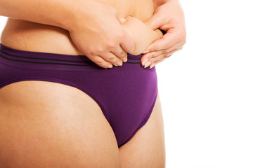 Woman measuring fat belly in underwear