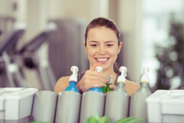 frau nimmt ein fitness-getränk im sportstudio