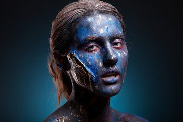 Blue face art woman with gold scar on face. Girl painted on blue