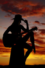 silhouette of a woman with a guitar hand on hat