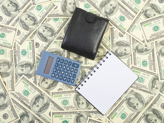 Calculator and notebook on a dollars background