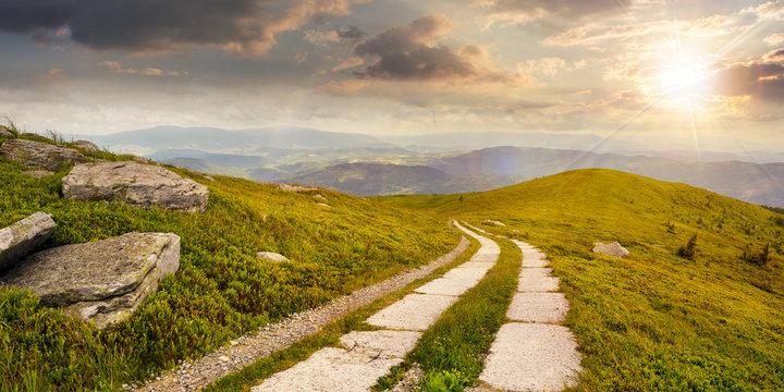 road on a hillside near mountain peak at sunset