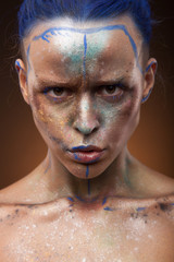 Portrait of a woman who is posing with blue and gold paint