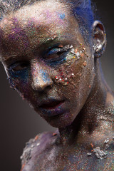 Beautiful face of a woman covered in glitter. Face art. Sexy