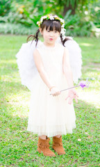Little girl in angel dress in the park