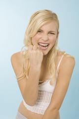 Porträt einer blonden Frau, die Anhebung der Faust, lachen