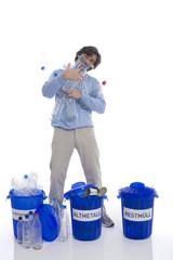 Man holding Kunststoff-Flaschen, stehend von Mülltonnen