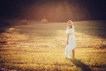 Girl dressed in  short dress on the field in sun light