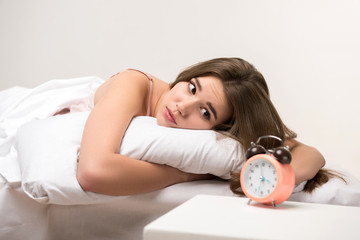 beauty lying on the bed with a clock