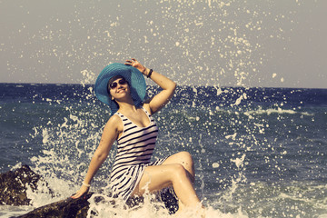 Woman sitting on a stone and splashing in the sea. Vintage style