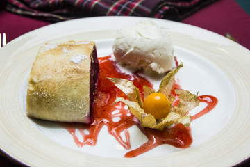 cherry strudel on a plate with red syrup