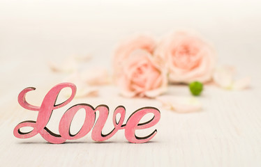 "Pink word ""love"" and roses on the background"